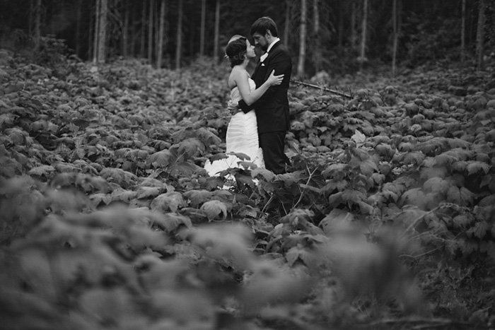 Bride and groom embrace in a wild raspberry field