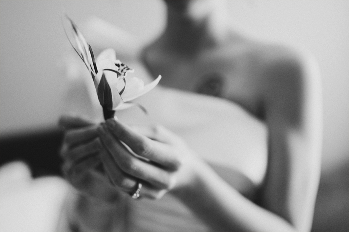 Bride preparing the boutonniere for her father on her wedding day