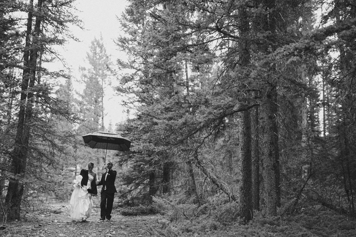 Bride and groom walking under an umbrella for portraits in the mountains